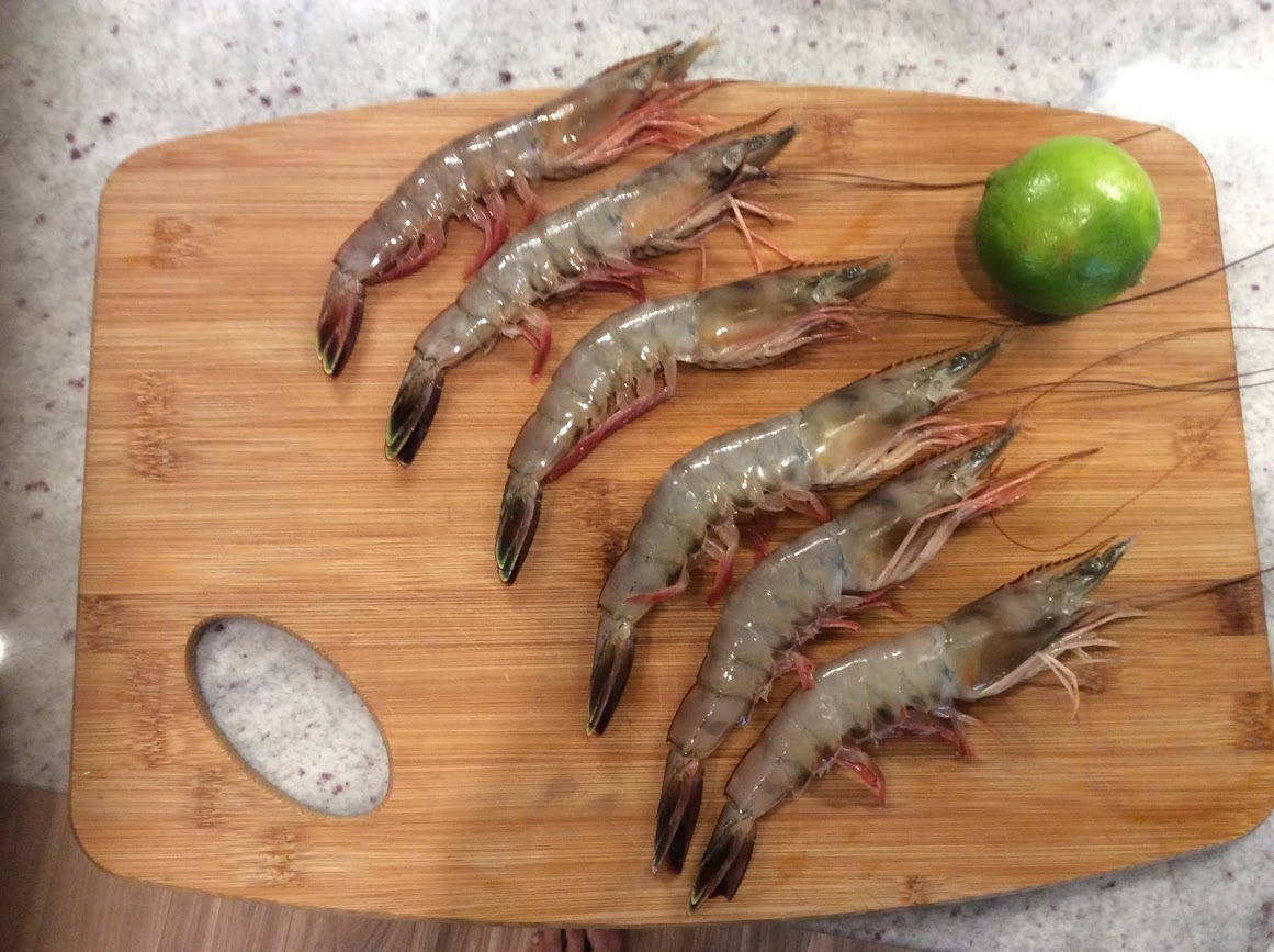 Picture showing six large shrimp on a cutting board.